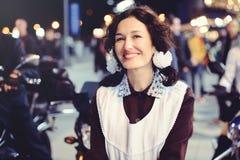 Mujer joven hermosa, peinado rizado y arcos en el aire abierto Feliz y sano vestidos en un uniforme escolar soviético Noche calie Fotografía de archivo libre de regalías