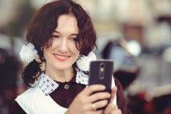 Mujer joven hermosa, peinado rizado y arcos en el aire abierto Feliz y sano vestidos en un uniforme escolar soviético saca o Imagenes de archivo