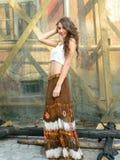Mujer joven hermosa, presentando en top del blanco y falda marrón larga, w Imagen de archivo