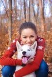 Mujer joven hermosa que abraza el perrito de los perros esquimales para un paseo en el parque imagenes de archivo