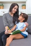 Mujer joven hermosa que abraza a su hermana que lee un libro en el sofá Foto de archivo libre de regalías