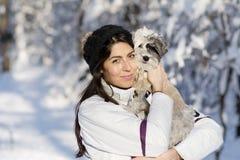 Mujer joven hermosa que abraza su pequeño perro blanco en el bosque del invierno tiempo que nieva Imagenes de archivo
