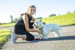 Mujer joven hermosa que activa con su perro Fotografía de archivo libre de regalías