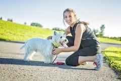 Mujer joven hermosa que activa con su perro Imagenes de archivo