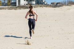 Mujer joven hermosa que activa en la playa, vista posterior imágenes de archivo libres de regalías