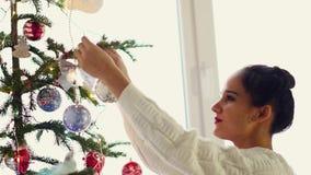 Mujer joven hermosa que adorna un árbol de navidad para la celebración de la Navidad almacen de metraje de vídeo