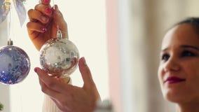 Mujer joven hermosa que adorna un árbol de navidad para la celebración de la Navidad metrajes