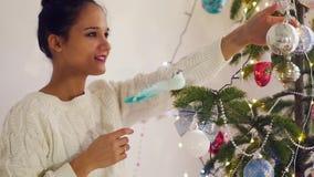 Mujer joven hermosa que adorna un árbol de navidad para la celebración de la Navidad almacen de video