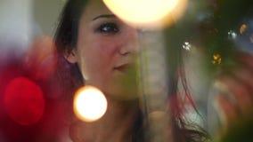 Mujer joven hermosa que adorna un árbol de navidad para la celebración de la Navidad Cara de una mujer en la Navidad almacen de video