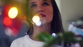 Mujer joven hermosa que adorna un árbol de navidad para la celebración de la Navidad Cara de una mujer en la Navidad almacen de metraje de vídeo