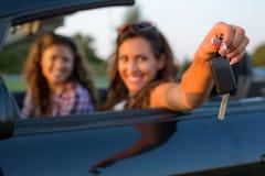 Mujer joven hermosa que alcanza hacia fuera llaves del coche a la cámara mientras que foto de archivo libre de regalías