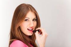 Mujer joven hermosa que aplica el lápiz labial fotos de archivo