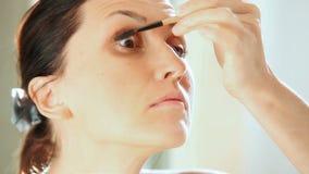 Mujer joven hermosa que aplica el rimel y que mira su reflexión en espejo almacen de metraje de vídeo