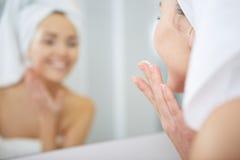 Mujer joven hermosa que aplica la crema hidratante facial Concepto de Skincare imagen de archivo libre de regalías