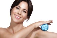 Mujer joven hermosa que aplica la herramienta del masaje en los brazos Imágenes de archivo libres de regalías
