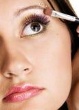 Mujer joven hermosa que aplica maquillaje foto de archivo