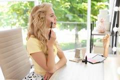 Mujer joven hermosa que aplica maquillaje foto de archivo libre de regalías