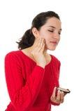 Mujer joven hermosa que aplica maquillaje Fotos de archivo libres de regalías