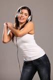 Mujer joven hermosa que baila y que canta a la música Imagen de archivo