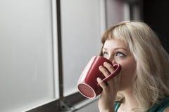 Mujer joven hermosa que bebe de la taza de café roja fotos de archivo