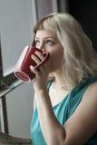 Mujer joven hermosa que bebe de la taza de café roja fotografía de archivo