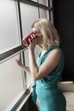 Mujer joven hermosa que bebe de la taza de café roja imagenes de archivo