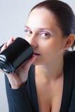 Mujer joven hermosa que bebe de una taza Imagen de archivo