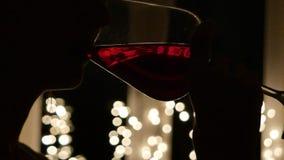 Mujer joven hermosa que bebe el vino rojo en la Navidad almacen de metraje de vídeo