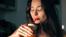 Mujer joven hermosa que bebe el zumo de naranja fresco en casa almacen de video