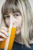 Jugo de consumición del mango de la mujer joven Imagen de archivo
