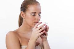 Mujer joven hermosa que bebe una taza de té caliente. Imagen de archivo