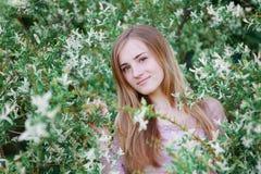 Mujer joven hermosa que camina en un jardín floreciente de la primavera Imagen de archivo libre de regalías