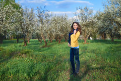 Mujer joven hermosa que camina en un jardín floreciente de la primavera Fotos de archivo libres de regalías