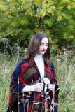 Mujer joven hermosa que camina a través de un campo de la hierba larga Foto de archivo