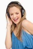 Mujer joven hermosa que canta mientras que escucha m Imagenes de archivo