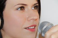 Mujer joven hermosa que canta y que escucha la música con los auriculares Foto de archivo libre de regalías