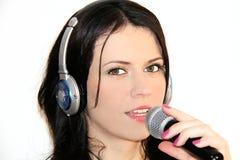 Mujer joven hermosa que canta y que escucha la música con los auriculares Imagenes de archivo