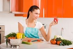 Mujer joven hermosa que cocina en la cocina Fotos de archivo