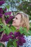 Mujer joven hermosa que coloca la lila cercana imagen de archivo