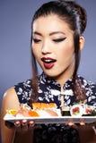 Mujer joven hermosa que come el sushi Foto de archivo libre de regalías