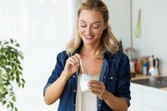 Mujer joven hermosa que come el yogur en casa fotografía de archivo