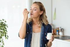 Mujer joven hermosa que come el yogur en casa fotos de archivo