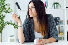 Mujer joven hermosa que come el yogur en casa Imagen de archivo
