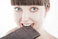 Mujer joven hermosa que come la barra de chocolate grande - (series) Fotos de archivo