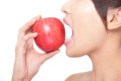 Mujer joven que come la manzana roja con los dientes de la salud Fotos de archivo