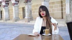 Mujer joven, hermosa que come un café en una calle metrajes