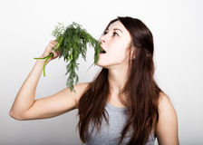 Mujer joven hermosa que come un eneldo comida sana - concepto fuerte de los dientes Fotografía de archivo
