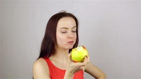 Mujer joven hermosa que come una manzana metrajes
