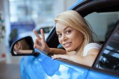 Mujer joven hermosa que compra el nuevo coche en la representación fotos de archivo