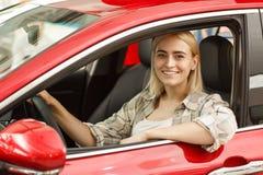 Mujer joven hermosa que compra el nuevo coche en la representación imagenes de archivo